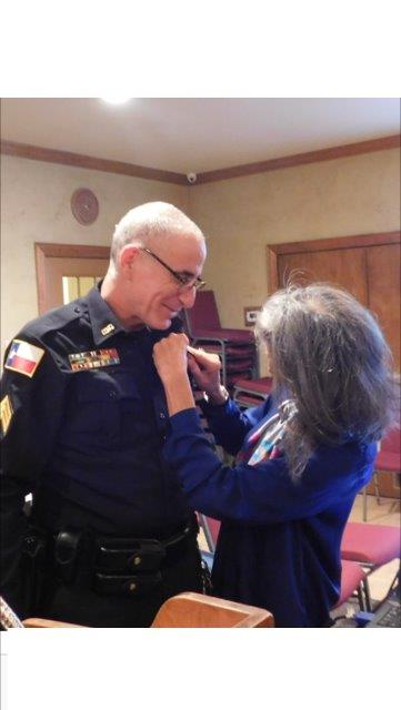 Sergenat Seif's wife pins new badge to his uniform